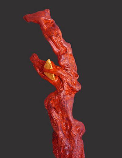 Einverleibte Kostbarkeit', Stein in Eichenwurzel, Fundort Eifel, mit Rot, Blau, Gold koloriert.